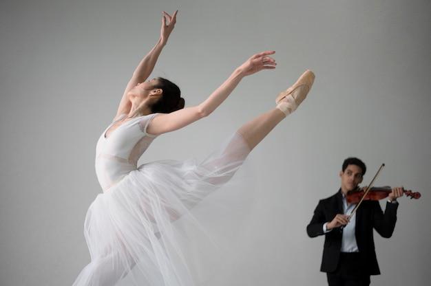 Ballerina tanzt im tutu-kleid und spielt geige Kostenlose Fotos