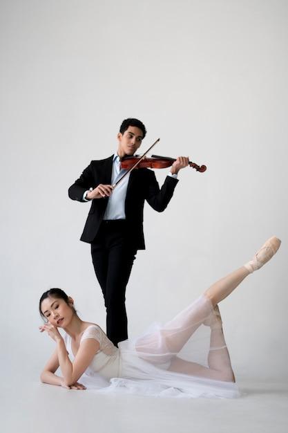 Ballerina und musiker poising zusammen Kostenlose Fotos
