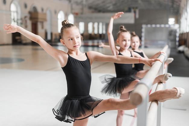 Ballerinamädchen im schwarzen ballettröckchen, das ihre beine auf stange ausdehnt Kostenlose Fotos