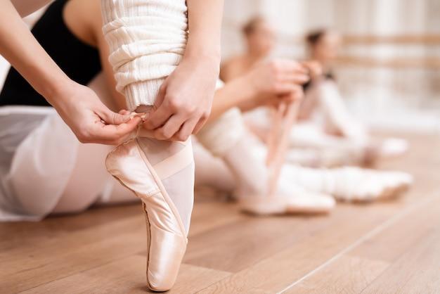 Ballerinas korrigieren spitzenschuhe im tanzsaal. Premium Fotos