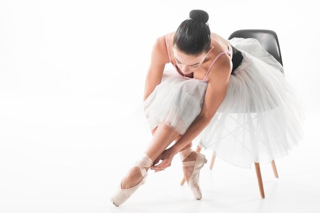 Balletttänzer, der auf dem stuhl bindet ballettschuhe gegen weißen hintergrund sitzt Kostenlose Fotos