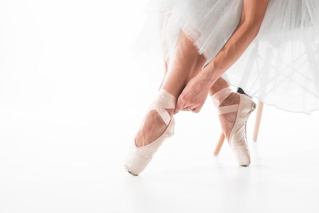 Balletttänzer, der ballettschuhe bindet Kostenlose Fotos