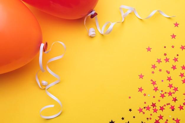 Ballone mit farbband und sternen auf orange hintergrund Kostenlose Fotos