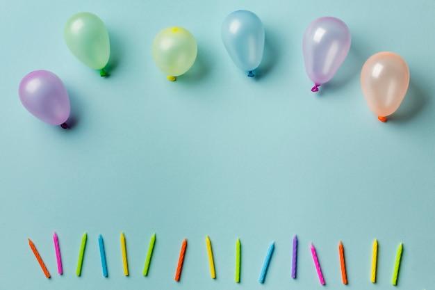 Ballone über der reihe von bunten kerzen gegen blauen hintergrund Kostenlose Fotos