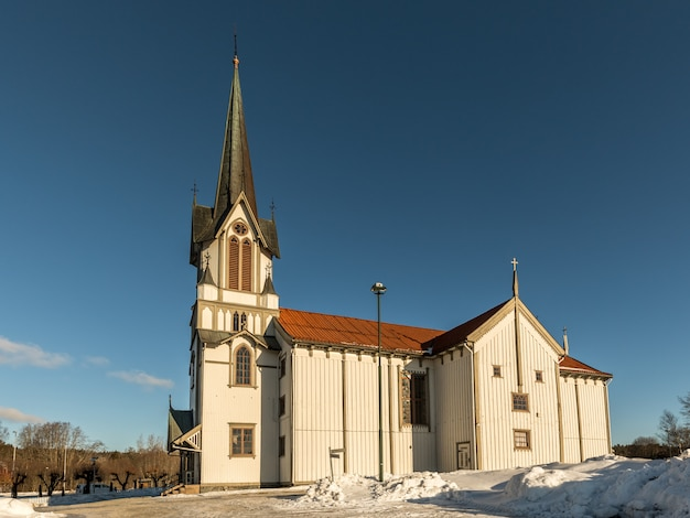 Bamble church, große hölzerne kirche aus dem jahr 1845. winter, schnee, sonnenschein und blauer himmel. seitenansicht. horizontales bild. Premium Fotos