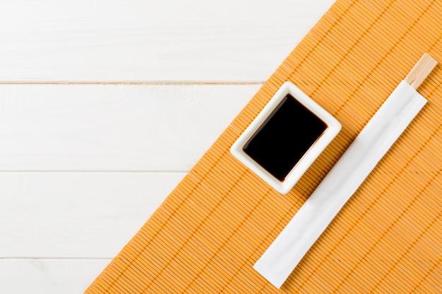 Bambusmatte und sojasoße mit sushiessstäbchen auf weißem holztisch Premium Fotos
