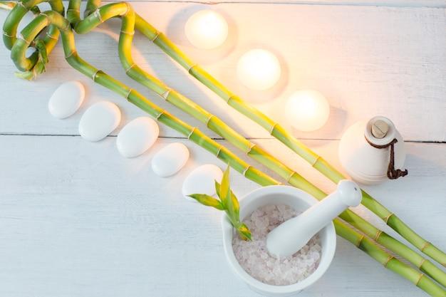 Bambusniederlassungen, öl, kerzen, seesalz und weiße steine (badekurort) auf einem weißen holztisch Premium Fotos