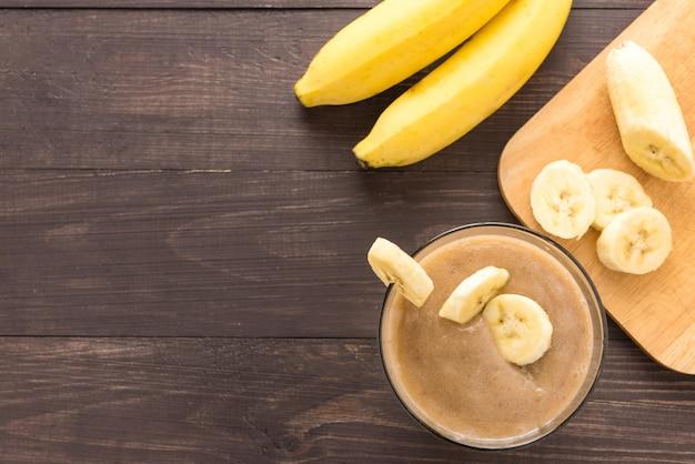 Banane smoothie auf hölzernem hintergrund. ansicht von oben Premium Fotos