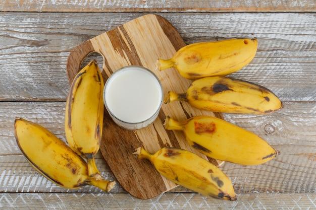 Bananen mit milch auf holz und schneidebrett, Kostenlose Fotos