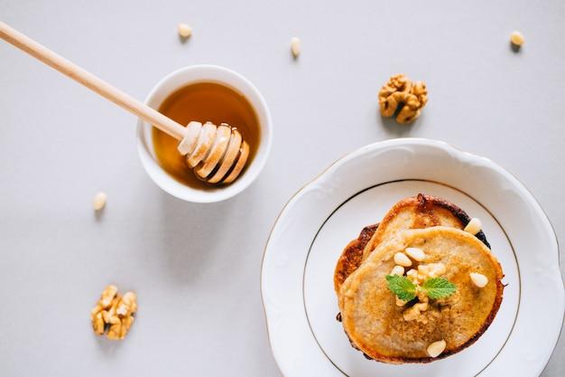 Bananenpfannkuchen der flachen lage mit walnüssen auf einem weißen hintergrund Premium Fotos