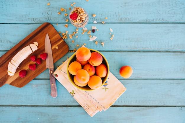Bananenscheiben; erdbeeren; pfirsich und hafer auf blauem hölzernem schreibtisch Kostenlose Fotos
