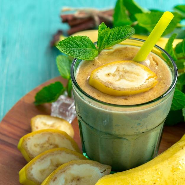 Bananensmoothie und frische banane auf holztisch. Premium Fotos