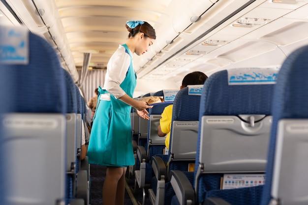 Bangkok airways flugbegleiter servieren den passagieren an bord speisen. Premium Fotos