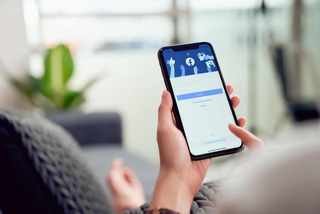 Bangkok, thailand - 28. januar 2020: frauenhand drückt den facebook-bildschirm auf apple iphone, soziale medien verwenden für informationsaustausch und vernetzung. Premium Fotos