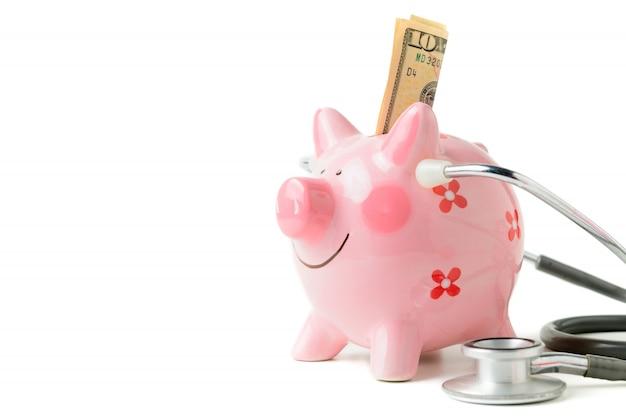 Banknote im sparschwein und im stethoskop lokalisiert Premium Fotos