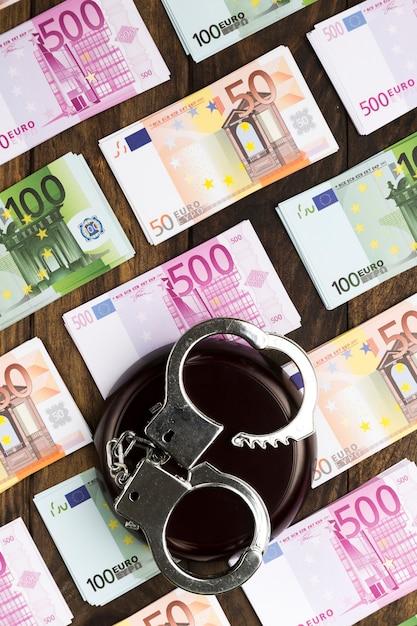 Banknoten auf holztisch mit handschellen und stand Kostenlose Fotos