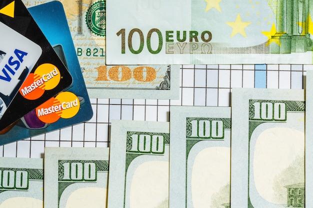 Banknoten von hundert euro und hundert dollar sind in der nähe von bankkarten auf karierter oberfläche. Premium Fotos