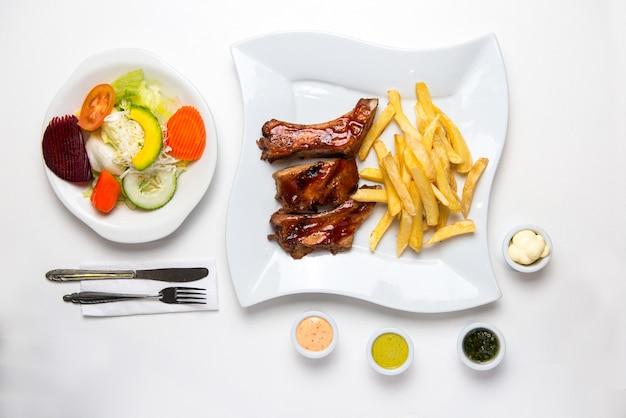 Barbecue ribs mit pommes frites, salat und sahne. bbq Premium Fotos