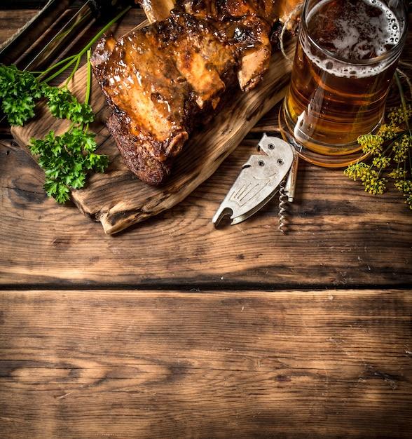 Barbecue-rippchen mit einem kalten bier. auf einem holztisch. Premium Fotos