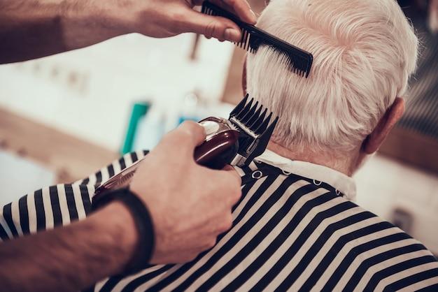 Barber shaves grey haired adult nacken mit rasiermesser Premium Fotos