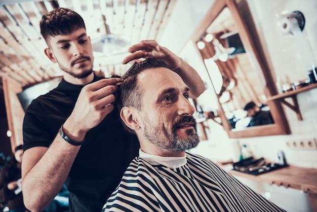 Barber shaves handsome smiling man mit rasiermesser. Premium Fotos