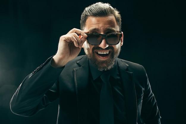 Bardenmann im anzug. stilvoller geschäftsmann auf schwarzem hintergrund. schönes männliches porträt. junger emotionaler mann. Kostenlose Fotos