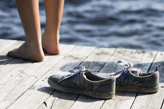Barfuß person, die nahe schmutzigen schuhen auf einem dock am meer steht Kostenlose Fotos