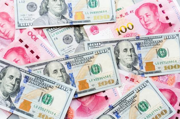 Bargeld: 100 amerikanische dollar und 100 chinesische yuan Premium Fotos