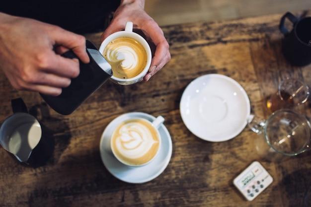 Barista bereitet cappuccino zu Kostenlose Fotos