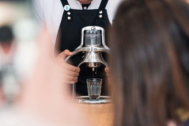 Barista bereitet kaffeegetränk zu Premium Fotos
