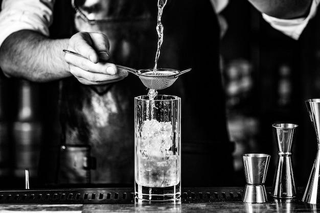 Barista bringt alkohol in ein cocktailglas mit sirup und eiswürfeln. Kostenlose Fotos