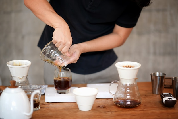 Barista, der auf dem tisch filterkaffee und zubehör herstellt Premium Fotos