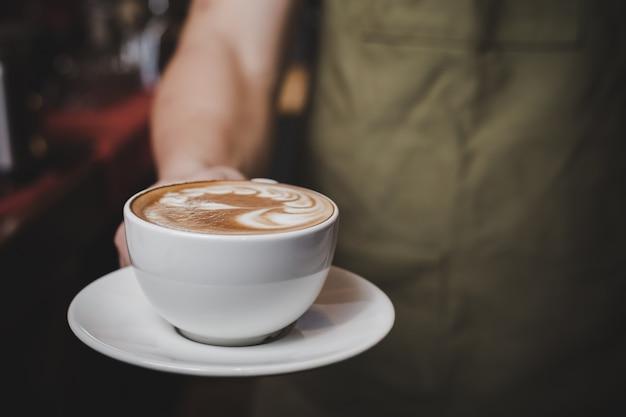 Barista, der hot cafe latte behandelt. Kostenlose Fotos
