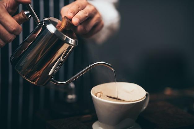 Barista gießt heißes wasser aus dem wasserkocher über das kaffeepulver, um den frisch gebrühten kaffee im kaffeecafé zu extrahieren. Premium Fotos