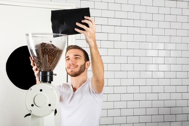 Barista gießt kaffeebohnen in die kaffeemaschine Kostenlose Fotos