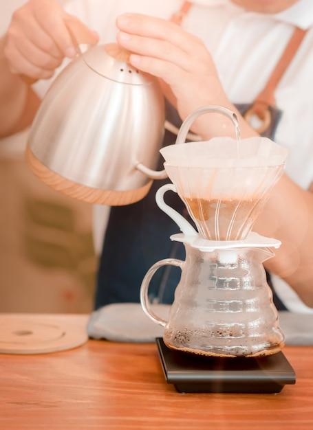 Barista-holding gießt heißes gekochtes wasser in eine kaffeekanne Premium Fotos