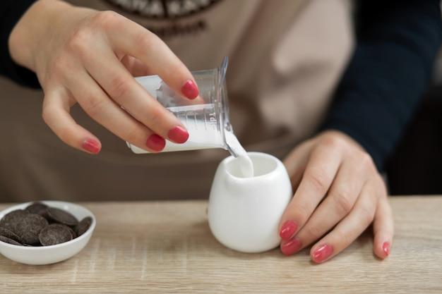 Barista in einer schürze gießt milch in eine tasse. barista arbeiten in einem café Premium Fotos