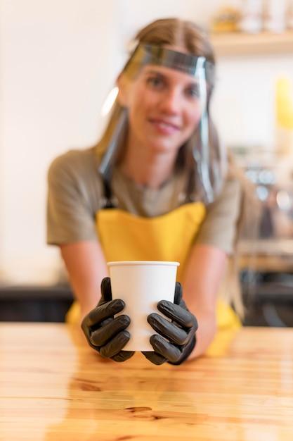 Barista trägt gesichtsschutz beim servieren von kaffee Kostenlose Fotos