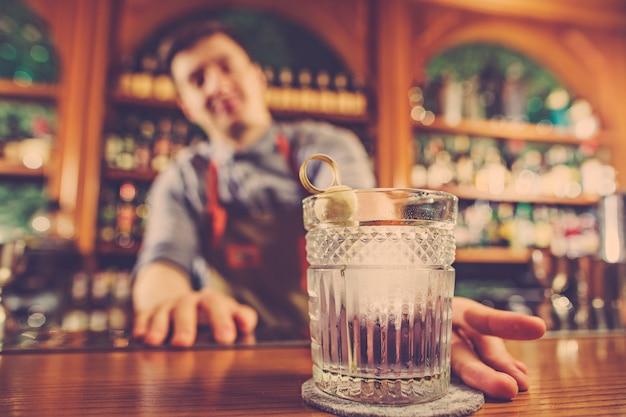 Barkeeper bietet einen alkoholischen cocktail an der bar an der bar Kostenlose Fotos