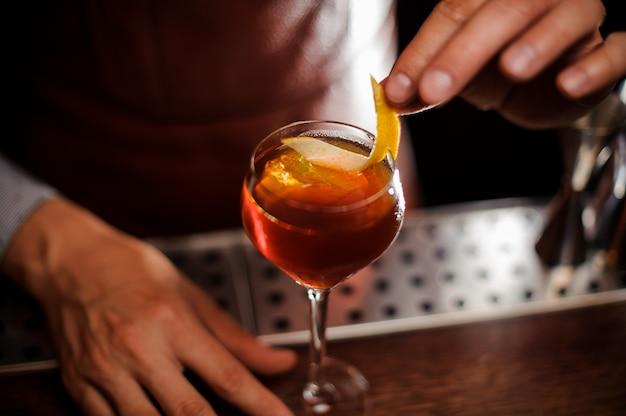 Barkeeper dekoriert einen cocktail mit zitronenschale Premium Fotos