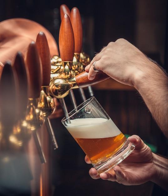 Barkeeper, der bier in glas setzt. Kostenlose Fotos