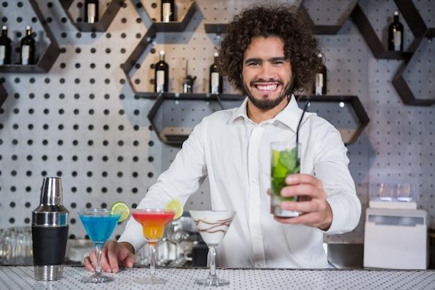 Barkeeper, der ein glas gin serviert Premium Fotos