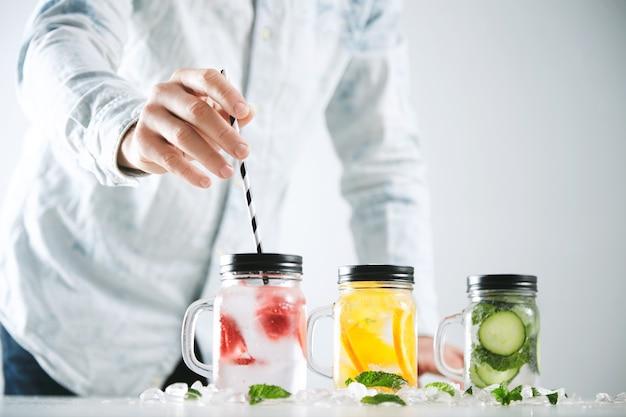 Barkeeper gibt gestreiftes trinkhalm in ein glas mit frischer kalter hausgemachter limonade aus eis, erdbeere, orange, gurke und minze. Kostenlose Fotos