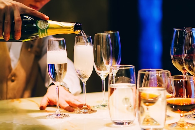 Barkeeper gießt champagner. kellner gießt champagner auf einer party. Premium Fotos