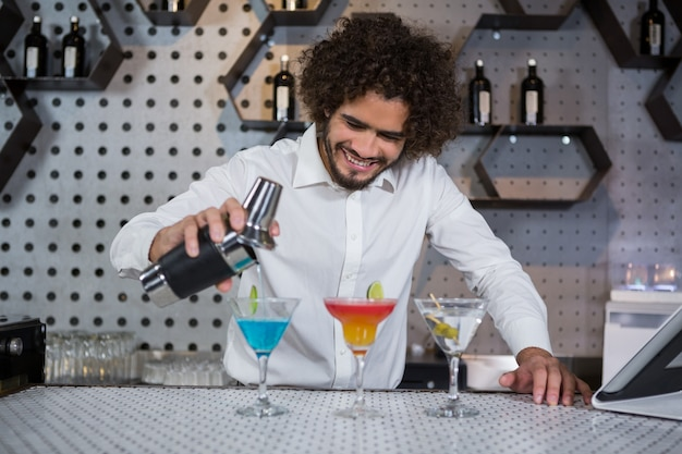 Barkeeper gießt cocktail in gläser Premium Fotos