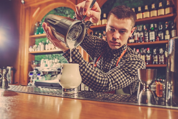 Barkeeper macht einen alkoholischen cocktail an der theke an der bar Kostenlose Fotos