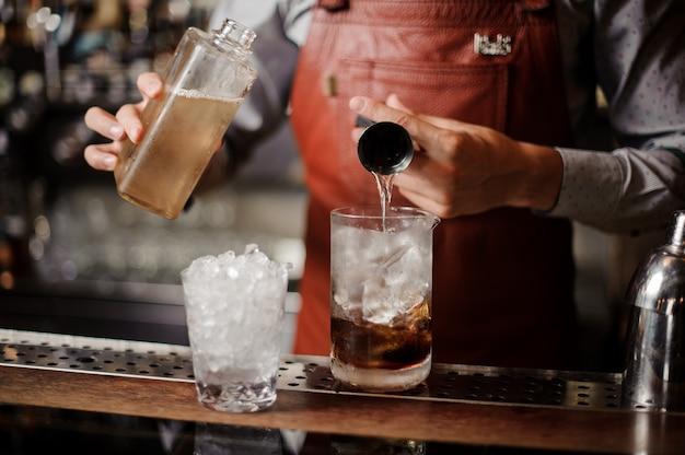 Barkeeper macht einen alkoholischen cocktail mit eis Premium Fotos