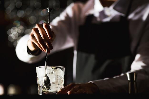 Barmann, der einen alkoholfreien cocktail in einem restaurant zubereitet. Premium Fotos