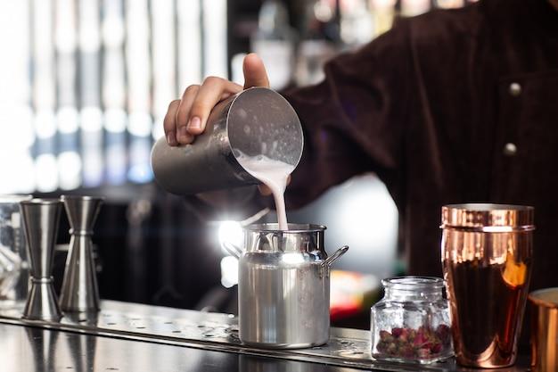 Barmann gießt den fertigen cocktail vorsichtig aus dem