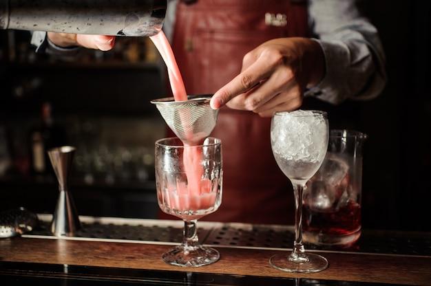 Barmann macht einen alkoholischen cocktail an der bar Premium Fotos